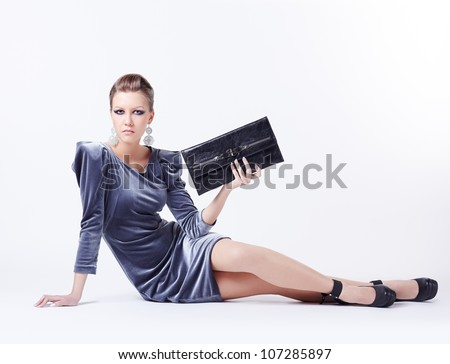 full-length portrait of beautiful young brunette woman in fancy dress sitting on the floor and holding clutch in hand