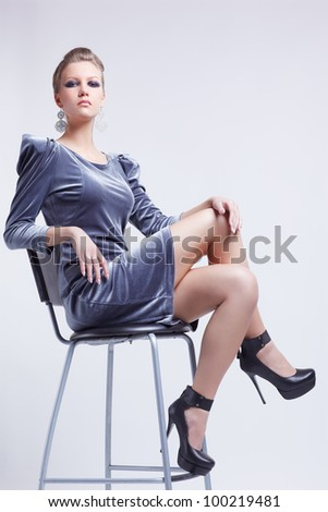 full-length portrait of beautiful young brunette woman in stylish dress sitting on bar chair
