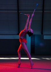 Full-length portrait of beautiful young girl, rhythmic gymnast isolated on colored background in neon light. Concept of motion, sport life, competition. Copy space for ad. Vertical composition