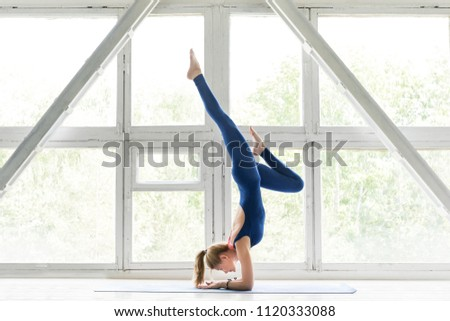 Full-length portrait of beautiful young woman wearing blue jumpsuit working out against vintage window, doing yoga or pilates exercise and handstand pose.