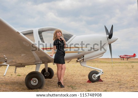 Full length portrait of blond woman leaning on the wing of the little white airplane