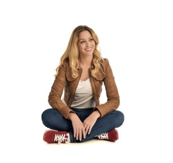full length portrait of blonde girl wearing brown leather jacket and jeans, seated pose on white background.
