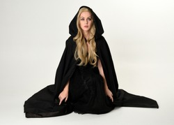 full length portrait of blonde girl wearing long black flowing cloak, sitting on the floor  with  a white studio background.