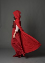 full length portrait of brunette girl wearing red fantasy costume with cloak, standing pose on a guy studio background.