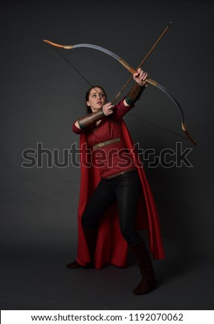 full length portrait of brunette girl wearing red medieval costume and cloak, holding a bow and arrow. standing pose on grey studio background. #1192070062