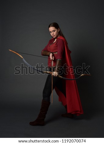 full length portrait of brunette girl wearing red medieval costume and cloak, holding a bow and arrow. standing pose on grey studio background. #1192070074