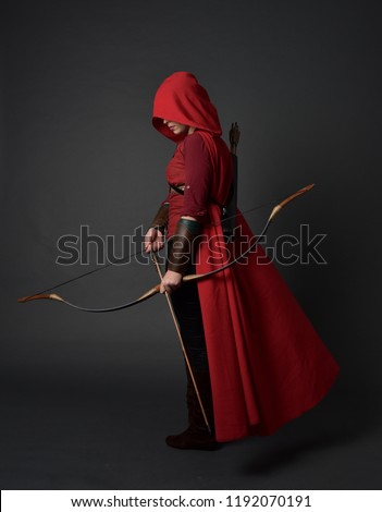 full length portrait of brunette girl wearing red medieval costume and cloak, holding a bow and arrow. standing pose on grey studio background. #1192070191