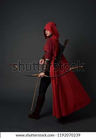 full length portrait of brunette girl wearing red medieval costume and cloak, holding a bow and arrow. standing pose on grey studio background. #1192070239