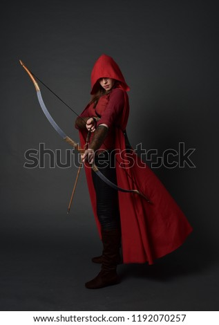 full length portrait of brunette girl wearing red medieval costume and cloak, holding a bow and arrow. standing pose on grey studio background. #1192070257