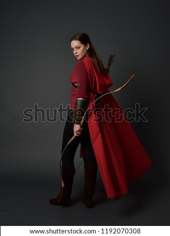 full length portrait of brunette girl wearing red medieval costume and cloak, holding a bow and arrow. standing pose on grey studio background. #1192070308