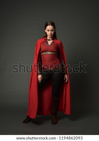full length portrait of brunette girl wearing red medieval costume and cloak. standing pose   on grey studio background. #1194862093