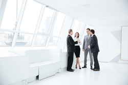 Full length portrait of Business team stand near the window in conference room