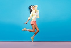 Full-length portrait of carefree brunette woman in shorts jumping while listening music. Indoor photo of adorable asian female model in yellow jacket fooling around in studio with blue walls.
