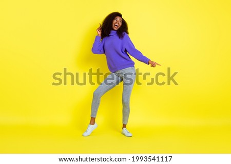 Full length portrait of carefree pretty dark skin person look empty space partying isolated on yellow color background