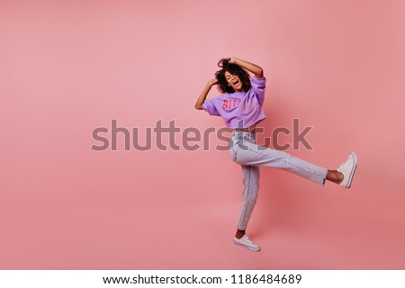 Full-length portrait of carefree slim lady in jeans. Blissful african woman dancing on rosy background.