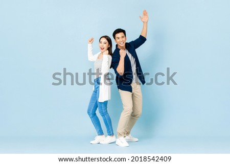 Full length portrait of cheerful Asian couple standing back to back smiling and clenching fists in light blue isolated studio background