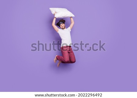 Full length portrait of cheerful carefree guy hold cushion above head toothy smile isolated on purple color background Foto stock ©