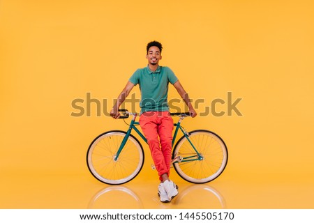 Full-length portrait of confident african man standing in front of his bike. Studio shot of emotional black guy in bright outfit posing with bicycle.