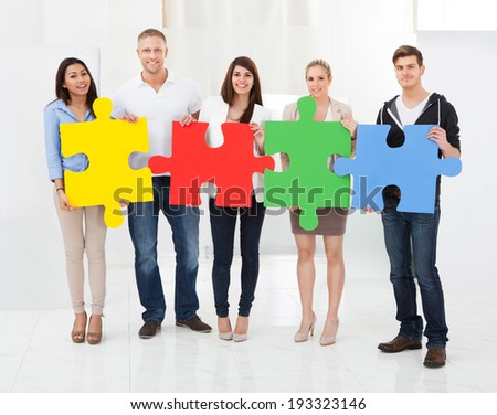 Full length portrait of confident businesspeople joining puzzle pieces in office