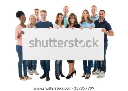Full length portrait of confident creative business team holding blank billboard against white background