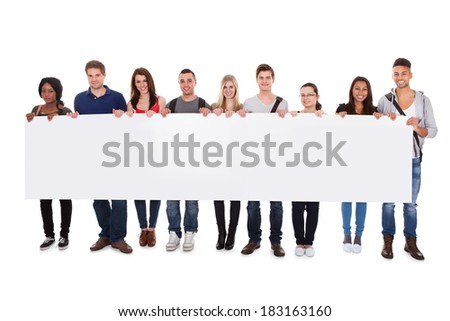 Full length portrait of confident multiethnic college students displaying blank billboard against white background