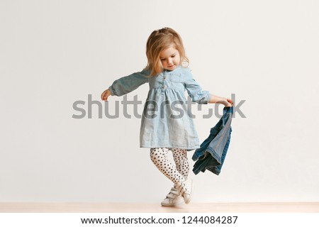 Full length portrait of cute little kid girl in stylish jeans clothes looking at camera and smiling, standing against white studio wall. Kids fashion concept #1244084287
