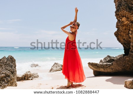 Stock Photo Full-length portrait of elegant european woman smiling during photoshoot near ocean. Stunning tanned girl in red posing on horizon background in morning.
