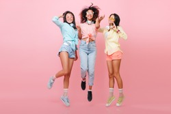 Full-length portrait of enthusiastic african girl in black shoes posing between international friends in pink studio. Sporty asian woman in blue shirt jumping near stylish ladies.