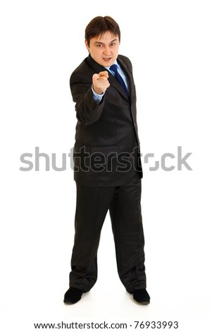 Full length portrait of evil businessman pointing finger at you isolated on white