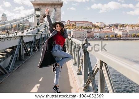 Full-length portrait of excited female traveler in vintage jeans dancing on bridge with cityscape on background. Photo of happy woman in long coat jumping during photoshoot in european town.