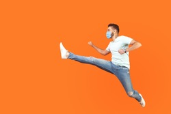 Full length portrait of excited man with surgical medical mask in casual style jumping over in air, running quickly fast, in hurry for discounts. indoor studio shot isolated on orange background