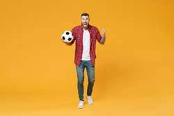 Full length portrait of excited young man football fan in red shirt cheer up support favorite team with soccer ball clenching fists isolated on yellow background studio. People sport leisure concept