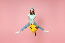 Full length portrait of excited young woman student in t-shirt hat glasses hold backpack jumping spreading legs isolated on pink background studio. Education in high school university college concept