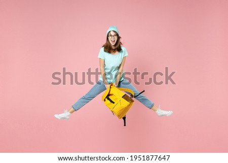 Full length portrait of excited young woman student in t-shirt hat glasses hold backpack jumping spreading legs isolated on pink background studio. Education in high school university college concept Сток-фото ©