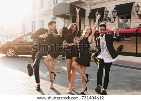 Full-length portrait of fascinating girl in elegant sandals dancing with boyfriend on the street while posing with friends. Outdoor photo of cheerful young people fooling around and drinking champagne #731404612