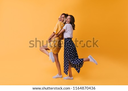 Full-length portrait of fascinating girl in long skirt dancing with friend. Glad female models in stylish clothes expressing happiness.