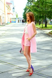 Full length portrait of fashionable it girl. Elegant woman in pink summer suit, street style concept.