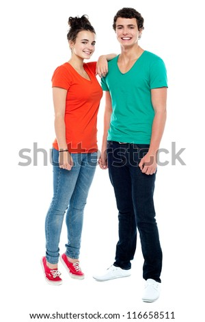 Full length portrait of fashionable young couple. Girl resting her hand on boy's shoulder - stock photo
