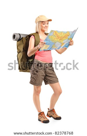 Full length portrait of female hiker looking at map isolated on white background