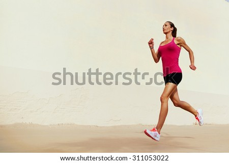 Full length portrait of female runner on morning jog against with copy space area wall for your text message or information, healthy sports woman with sexy figure playing sports outdoors in summer day #311053022