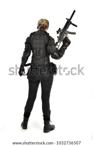 Stock Photo full length portrait of female  soldier wearing black  tactical armour  holding a gun, isolated on white studio background.