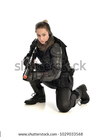 Stock Photo full length portrait of female wearing black  tactical armour holding a gun, crouching pose, isolated on white studio background.
