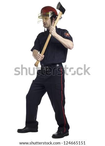 Full length portrait of fireman holding axe against white background