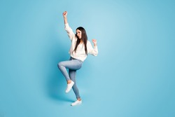 Full length portrait of funny adorable girl dancing raise knee hands isolated on blue color background