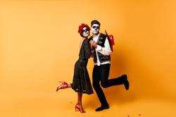Full-length portrait of funny zombies dancing in studio. Indoor photo of dead couple celebrating halloween together.