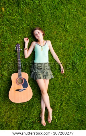 Full length portrait of girl lying down on grass in the park with a guitar
