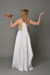 full length portrait of girl wearing white ancient Greek or Roman costume, standing pose on a grey background.