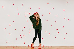 Full-length portrait of girl with light-brown hair standing under heart confetti. Indoor photo of adorable female model in red sandals dancing on white background.