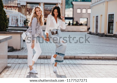 Full-length portrait of good-looking ladies dancing with happy smile. Outdoor photo of well-dressed friends walking together down the street.