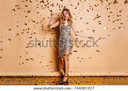 Full-length portrait of graceful fair-haired woman in trendy attire chilling at christmas party. Joyful caucasian female model with curly hair having fun during photoshoot with confetti. #744085927
